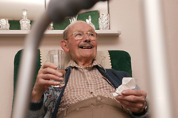 Elderly man drinking a glass of water; homecare for the elderly,