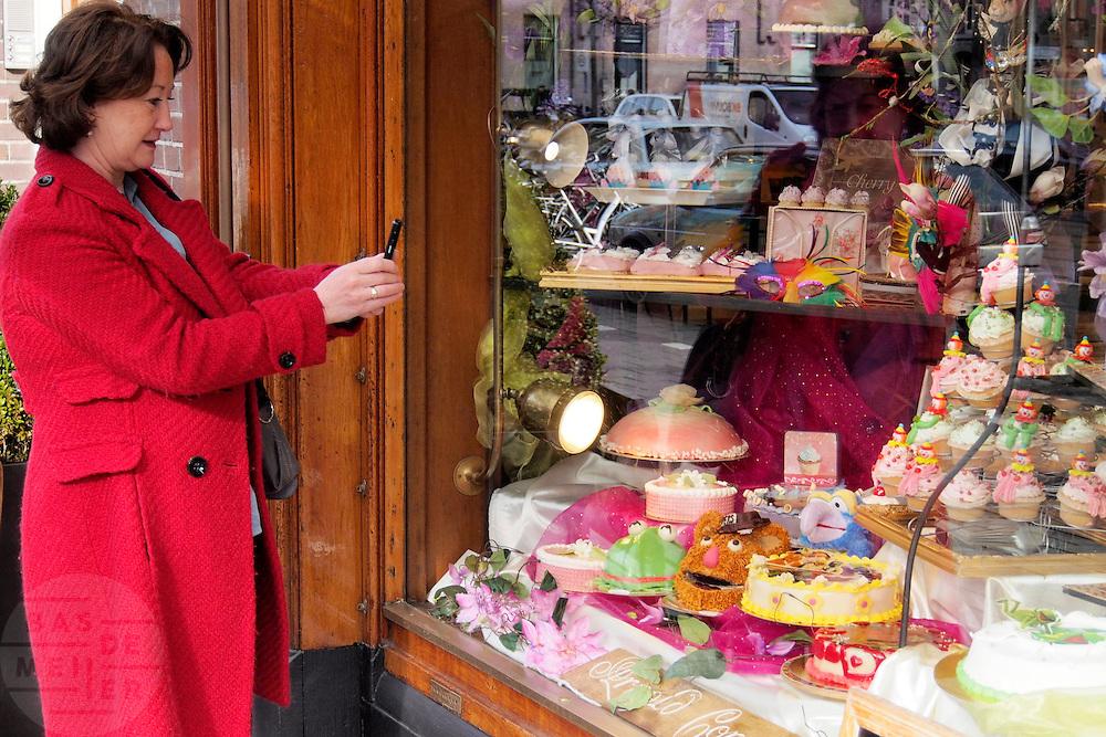 Een vrouw maakt met haar mobiele telefoon een foto van een etalage met Muppetpoppen.<br /> <br /> A woman is photographing with a cell phone a window of a bakery showing some Muppet faces.