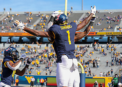 Nov 14, 2020; Morgantown, West Virginia, USA; West Virginia Mountaineers wide receiver T.J. Simmons (1) celebrates with teammates after catching a touchdown pass during the second quarter against the TCU Horned Frogs at Mountaineer Field at Milan Puskar Stadium. Mandatory Credit: Ben Queen-USA TODAY Sports