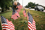 10 SEPTEMBER 2020 - DES MOINES, IOWA: A volunteer sets out American flags along Fleur Dr. on the shore of Gray's Lake. About 25 volunteers braved cold and rainy weather Thursday to line the west end of Gray's Lake in Des Moines with American flags. The display of flags was a part of an annual event called the 9/11 Tribute Trail. About 3,000 flags were set out in memorial of the 3,000 people killed in the 9/11 terrorist attacks.    PHOTO BY JACK KURTZ