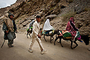 A family walks along the side of the road near Hajigak, one of the largest undeveloped iron ore reserves in the world.
