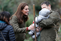 The Duchess of Cambridge meets a young baby during a visit to the King Henry's Walk Garden in Islington, London to learn about a project bringing people together through a shared love of horticulture.