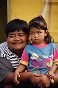 Father and daughter watch a parade for the patron saint of the village of Malojloj on the South Island. U.S. Territory of Guam, an island in the Western Pacific Ocean, the largest of the Mariana Islands.