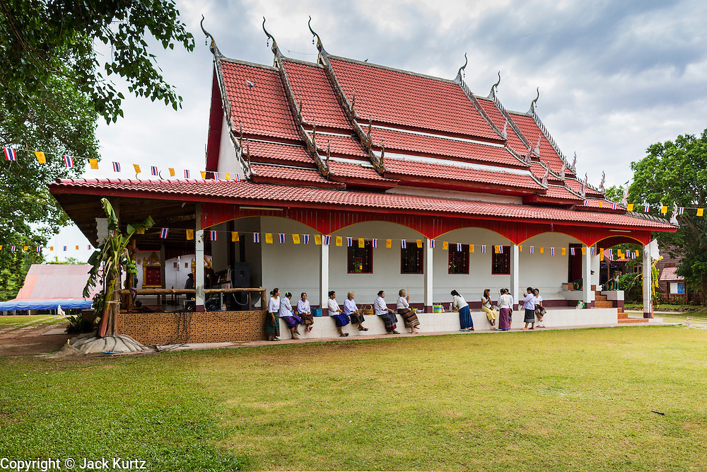 29 JUNE 2014 - DAN SAI, LOEI, THAILAND: Women wait to go into Wat Ponchai on the last morning of the Ghost Festival. Phi Ta Khon (also spelled Pee Ta Khon) is the Ghost Festival. Over three days, the town's residents invite protection from Phra U-pakut, the spirit that lives in the Mun River, which runs through Dan Sai. People in the town and surrounding villages wear costumes made of patchwork and ornate masks and are thought be ghosts who were awoken from the dead when Vessantra Jataka (one of the Buddhas) came out of the forest. On the last day of the festival people participate in merit making ceremonies at the Wat Ponchai in Dan Sai and lead processions through town soliciting donations for the temple.    PHOTO BY JACK KURTZ