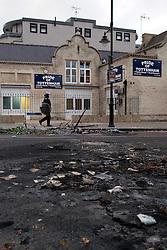"© Licensed to London News Pictures . FILE PICTURE DATED 07/08/2011 . Tottenham , UK . A lone riot policeman walks by the "" Pride of Tottenham "" pub on Tottenham High Road as all around lies damage and devastation following a night of rioting . Photo credit : Joel Goodman/LNP"