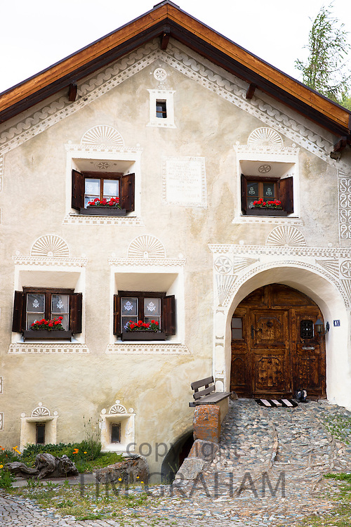 House in the Engadine Valley in the village of Guarda with old painted stone 17th Century buildings, Switzerland