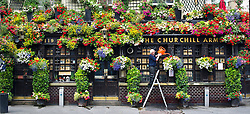 © London News Pictures. 26/07/2013 . London, UK.  Gerry O'Brien, landlord of the Churchill Arms on Kensington Church road, West London, waters the flowers on his pub on a summers day. Gerry, who has been the landlord of the CHurchill Arms for 30 years, spends 2 weeks every year planting the flowers which are watered twice a day.  Photo credit : Ben Cawthra/LNP