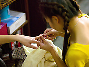 Manicure at Sengsavang beauty salon, a social enterprise supported by AFESIP Laos which offers beauty training and an income generating activity that supports former victims of trafficking to return to a normal life through a sustainable community reintegration. AFESIP (Agir pour les Femmes en Situation Precaire / Acting for Women in Distressing Situations) is a French non-governmental, non-partisan and non-religious organisation which combats the causes and consequences of trafficking and sexual exploitation of women and girls.