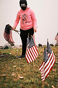 10 SEPTEMBER 2020 - DES MOINES, IOWA: A volunteer puts out American flags on the shore of Gray's Lake. About 25 volunteers braved cold and rainy weather Thursday to line the west end of Gray's Lake in Des Moines with American flags. The display of flags was a part of an annual event called the 9/11 Tribute Trail. About 3,000 flags were set out in memorial of the 3,000 people killed in the 9/11 terrorist attacks.    PHOTO BY JACK KURTZ