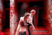 """V. 13. Valencia, 31/08/2005. Una pareja se retira tras la fiesta de la """"tomatina"""" de Buñol, Valencia, en la que cerca de 40.000 personas se han lanzardo durante una hora 120 toneladas de tomates maduros, una tradición que cuenta ya con 60 años de antigüedad. EFE/Kai Försterling."""