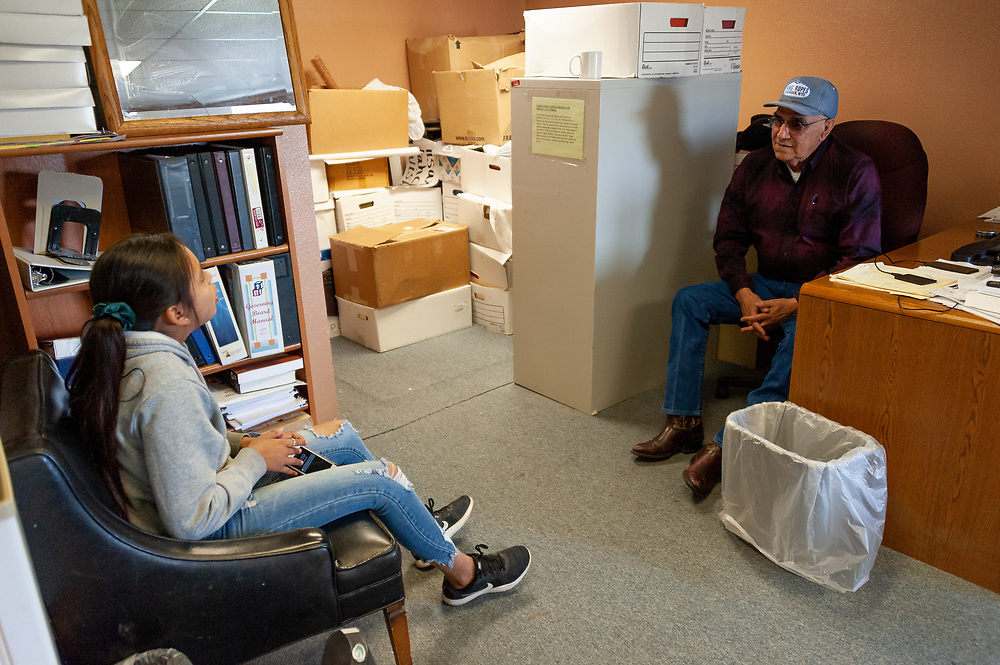 Calvin Herrera, Clayvin's father and cabinet head of the Crow Tribe Education Department, in his office with his granddaughter, Twoots.
