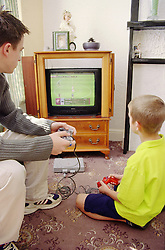 Two boys playing on playstation in front room,