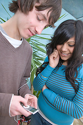Teenagers listening to music on an MP3 player,