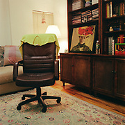 A black desk chair with a green sweater hanging over the back in the center of a room, on an ornate Oriental carpet, with a couch behind it and a lamp in the corner. There is a large wooden bookcase / storate unit to the right with a painting of a woman with a floral hat resting on the main shelf.