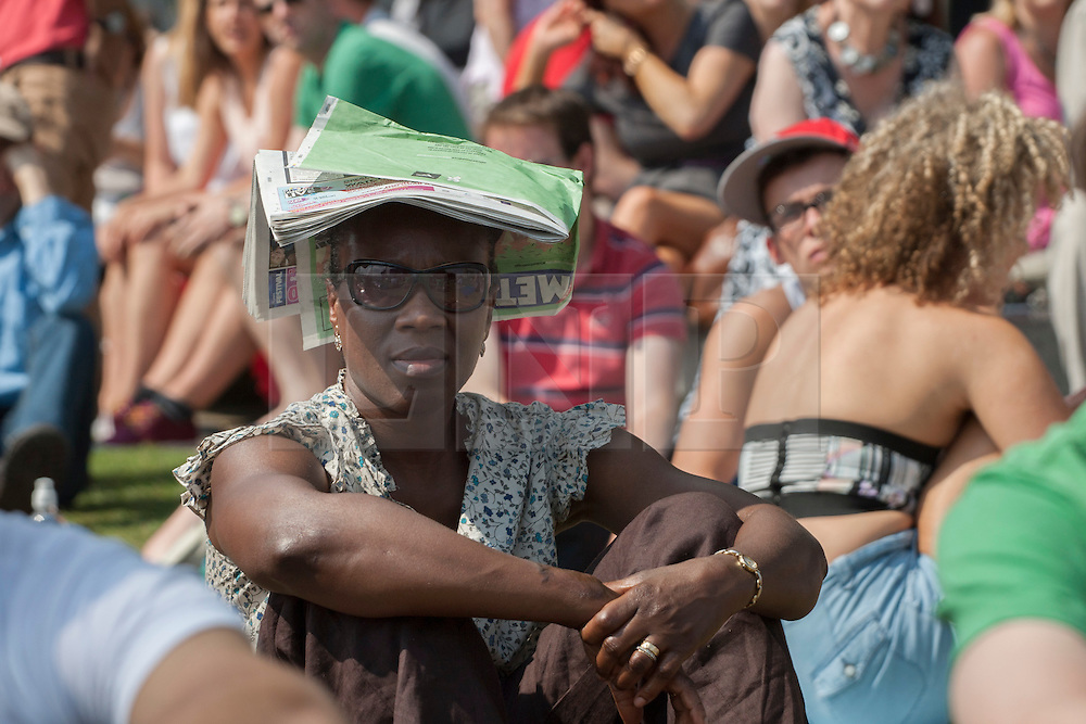 © licensed to London News Pictures. London, UK 10/08/2012. A woman shelters her head with a newspaper as people enjoying hot weather and watching the Games in Potters Fields Park on 10/08/12. Photo credit: Tolga Akmen/LNP