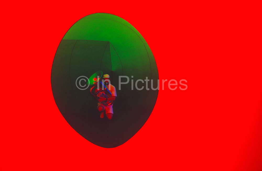 A lone musician kneels to play the tuba within an oval aperture in the art installation sculpture known as Colourscape on Clapham Common, South London, England. Created by an outside overhead sun shining through a collection of large, inflatable PVC domes, the man walks slowly through tunnels, enticing customers to ecperience vivid colour while emitting eerie sound from voices, brass and string instruments. Designed by Simon Desorgher & Lawrence Casserley, Colourscape celebrated its 10th year of installation in Clapham in 2004. Colourscape's charitable Trust, Nettlefold Arts, was founded in 1988, with the purpose of presenting contemporary music, related arts and educational events, in innovative ways.