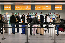 © Licensed to London News Pictures. 17/05/2021. Crawley, UK. Passengers line up at EasyJet self check-in desks at Gatwick Airport as step three on the roadmap out of lockdown begins. Travel to 12 countries on the green list is allowed from today. Holiday-makers returning home from green listed countries, including Portugal, Gibraltar and Iceland will not have to self-isolate on return. Various hospitality rules are also changing today - with pubs and restaurants allowed to serve seated customers indoors. Photo credit: Peter Macdiarmid/LNP
