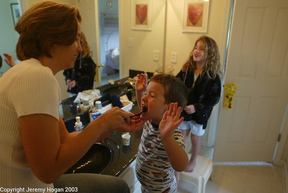Lourdes Heumann helps her son Ryan brush his teeth.