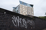 Exterior detail of The Cube building behind an old wall covered in graffiti on 7th October 2020  in Birmingham, United Kingdom.  The Cube is a 25 storey mixed-use development in the centre of Birmingham, England. Designed by Ken Shuttleworth of MAKE Architects, it contains 135 flats, offices, shops, a hotel and a restaurant. It is the final phase of The Mailbox development.