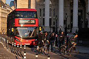 With the columns of Royal Exchange in the background, cyclists and a London bus are queued at a red light in at Bank Triangle and  in the City of London, the capitals financial district, on 27th February 2021, in London, England.