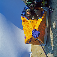 """Alex Lowe relaxes in a hanging Portaledge camp 1700 feet above the glacier on Rakekniven (""""The Razor""""), a massive overhanging cliff in the Filchner Mountains of Queen Maud Land Antarctica."""