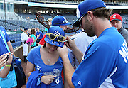 Kansas City Royals fan Amber Brooks, left, has her moose hat signed by her favorite player, Mike Moustakas, right, before their game against the Tampa Rays at Kauffman Stadium in Kansas City, Mo., Tuesday, April 30, 2013.  (AP Photo/Colin E. Braley).