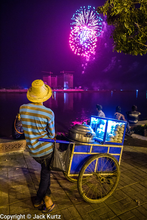 02 FEBRUARY 2013 - PHNOM PENH, CAMBODIA:  A snack vendor and other Cambodians watch a fireworks display to honor former King Norodom Sihanouk over the Mekong River. Much of Phnom Penh has been shut down to honor former King Norodom Sihanouk, who ruled Cambodia from independence in 1953 until he was overthrown by a military coup in 1970. Only bars, restaurants and hotels that cater to foreign tourists are supposed to be open. The only music being played publicly is classical Khmer music. Sihanouk died in Beijing, China, in October 2012 and will be cremated during a state funeral royal ceremony on Monday, Feb. 4.    PHOTO BY JACK KURTZ