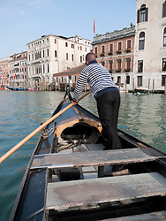Gondolier on public Traghetto ferry gondola crossing the Grand Canal in Venice Italy