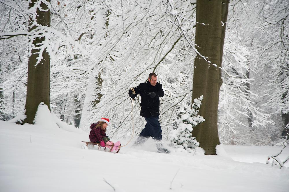 Nederland, Driebergen, 19  dec 2010.Winterplaatjes in Driebergen na forse sneeuwval. Er viel zo'n 20 cm sneeuw. Ouders met kinderen op sleetjes vermaken zich in  de bosachtige omgeving van Driebergen. ..Foto (c)  Michiel Wijnbergh