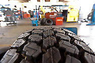 The interior of an automobile tire and repair shop is seen in the background of  a closeup view of tire tread. WATERMARKS WILL NOT APPEAR ON PRINTS OR LICENSED IMAGES.