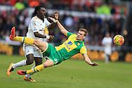 Bafetimbi Gomis of Swansea city (l) collides with Ryan Bennett of Norwich as they go for the ball. Barclays Premier league match, Swansea city v Norwich city at the Liberty Stadium in Swansea, South Wales  on Saturday 5th March 2016.<br /> pic by  Andrew Orchard, Andrew Orchard sports photography.