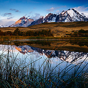 Los Cuernos towers and the Paine Massive get bathed with the first light of sunrise while a pond highlights a rare reflection in Torres del Paine National Park, Chile.