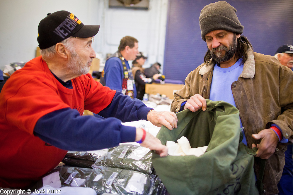 04 FEBRUARY 2011 - PHOENIX, AZ: BERNARD KAPLAN (left) a US Army veteran of the Korean and Vietnam Wars, helps DANIEL FURRER, a homeless Army vet, pick out some clean clothes at the Arizona StandDown Friday. The Arizona StandDown is an annualthree day event that brings together the Valley's homeless and at-risk militaryveterans, connecting themwith services ranging from: VA HealthCare, mental health services, clothing, meals, emergency shelter, transitional and permanent housing, ID/ drivers license's, court services and Legal Aide, showers, haircuts and myriad other services and resources. Arizona StandDown isheld annually at the Veterans Memorial Coliseum at the Arizona State Fairgrounds in Phoenixon Super Bowl weekend.    Photo by Jack Kurtz