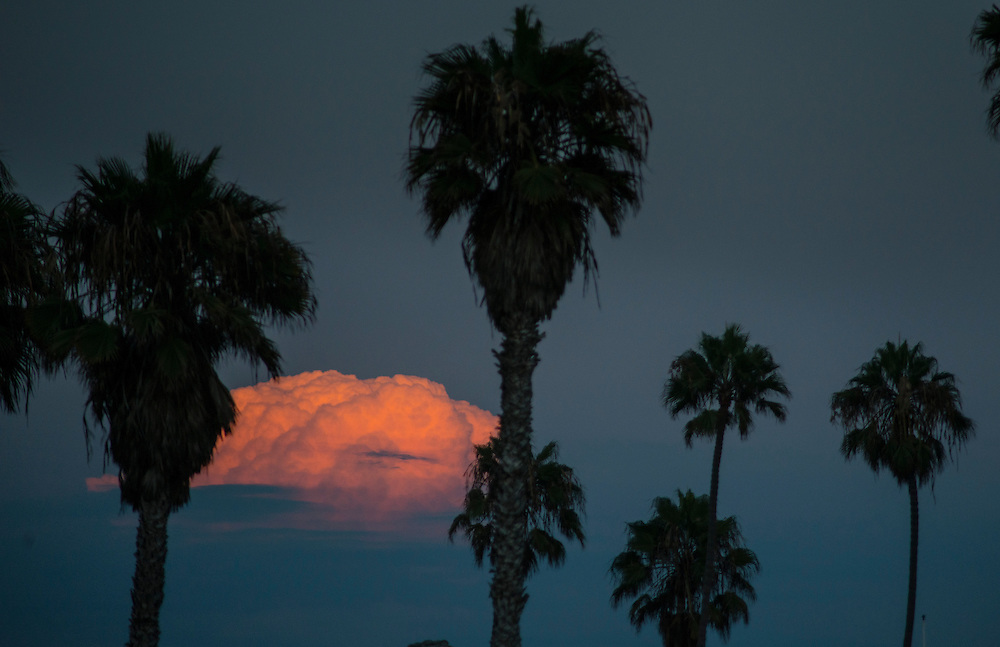 A storm cloud moves in during sunset at Pacific Beach, CA.