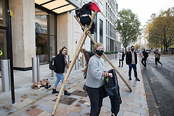 London, UK. 10 November, 2020. Environmental activists from Extinction Rebellion erect a tripod to protest outside the Shell Centre on the 25th anniversary of the killings of the Ogoni Nine. The Ogoni Nine, leaders of the Movement for the Survival of the Ogoni People (MOSOP), were executed by the Nigerian government in 1995 after having led a series of peaceful marches involving an estimated 300,000 Ogoni people against the environmental degradation of the land and waters of Ogoniland by Shell and to demand both a share of oil revenue and greater political autonomy.