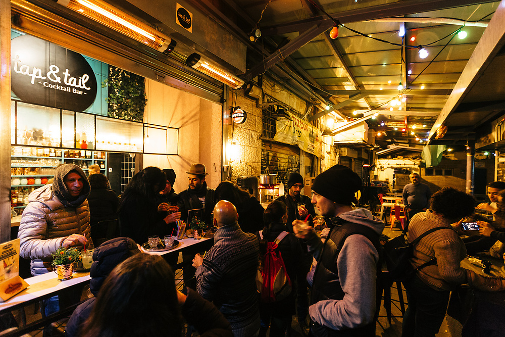 Customers enjoy alcoholic drinks at the Tap & Tail bar at the heart of Mahane Yehuda Market, often called 'The Shuk'  in Jerusalem, Israel, on November 21, 2017.
