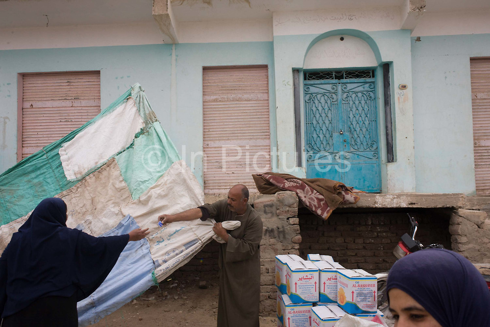A stallholder erects a shelter from the sun at the weekly market at Qurna, a village on the West Bank of Luxor, Nile Valley, Egypt. Handing over a box of matches to another, a woman whose hand is also outstretched to reach across the homemade sheeting. Amidst the bustle of this busy regular event, people from many miles around have come to trade and buy their provisions.