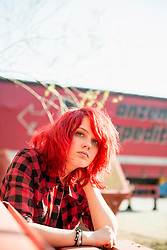Confident teenage girl piercing bright red hair