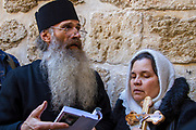 An Orthodox Christian priest and parishoner visit outside the main entrance to the Church of the Holy Sepulchre.