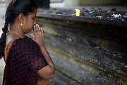 A woman offers prayers after lighting an oil lamp outside the Murugan temple in Swamimalai, Tamil Nadu, India