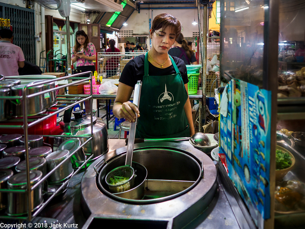 10 JULY 2018 - NAKHON PATHOM, THAILAND:  A food vender makes noodle soup in the market in Nakhon Pathom. Nakhon Pathom is about 35 miles west of Bangkok. It is one of the oldest cities in Thailand, archeological evidence suggests there was a settlement on the site of present Nakhon Pathom in the 6th century CE, centuries before the Siamese empires existed. The city is widely considered the first Buddhist community in Thailand and the nearly 400 foot tall Phra Pathom Chedi is considered the first Buddhist temple in Thailand.    PHOTO BY JACK KURTZ