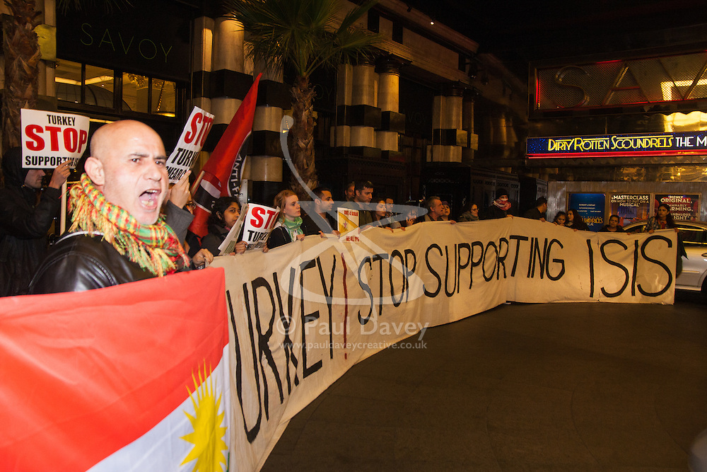 """London, October 25th 2014. Dozens of Britain's Kurdish community and their supporters demonstrated outside the exclusive Savoy as Turkey's ambassador welcomed guests to a ball. The Kurds accuse Turkey of helping Jihadists from ISIS in eradicating Kurds, who have held a long campaign for an autonomous Kurdish state. Pictured: Protesters demand that """"Turkey stops supporting ISIS"""""""