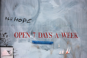 A shop window in Camden north London proclaims in red stencilled letters the business is open seven days a week when the store has gone out of business and the words No Hope have been added after the pane of glass has been white-washed. Stickers have been applied and torn off again. It is a graphic picture of irony and delusion, a misguided shop owner who thought his company was successful when it was heading for closure.
