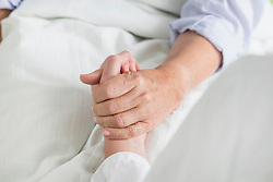 Woman holding patient's hand