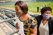 17 SEPTEMBER 2020 - DES MOINES, IOWA: NUNEE SIAH TARLEY, left, clutches her naturalization certificate as she and a friend walk out of the stadium after a naturalization ceremony at Principal Park, a minor league baseball stadium in downtown Des Moines. About 75 people from 32 countries were naturalized as US citizens Thursday. It was the last citizenship ceremony in Des Moines before citizenship fees dramatically increase. Starting Oct. 2, the fee to apply for U.S. citizenship will increase from $640 to $1,160 if filed online, or $ 1,170 in paper filing, a more than 80% increase in cost. Advocates for immigration are afraid the new fees will be too expensive for many immigrants and say it's an effort by the Trump Administration to limit the number of new citizens welcomed into the United States. Because of the COVID-19 pandemic, there has been dramatic slow down in the number of naturalization ceremonies this year.          PHOTO BY JACK KURTZ
