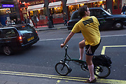 Wearing shorts, long socks, slippers and a t-shirt on an otherwise cold autumn afternoon, a male cyclist looks over shoulder before re-joining traffic flow on busy Charing Cross Road in central London. His bike is of a foldaway Brompton-style design, such that can collapse into a small carry-on bundle that can be accommodated on public transport like trains. A London taxi drives past at speed near Leicester Square underground station in the heart of Theatreland.