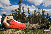 Hiker Dallas Anderson takes a nap on the trail to Goat Lake, Goat Rocks Wilderness, Washington.