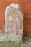 Rune stone outside the cathedral dating from the 11th century. The stone was put up by Tyke as a memorial after the death of Gunnar, son of Grim. Vaxjo town. Smaland region. Sweden, Europe.