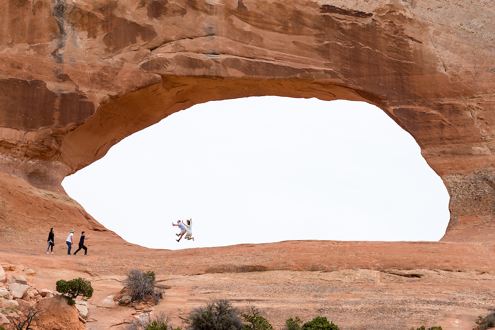Jumping for photograph in Wilson Arch, Utah.