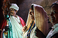 A devotee is waiting to receive the blessing of the cross from a priest in one of the churches of Lalibela. The veneration and kiss of the cross is one of the characteristic aspects in the Ethiopian Orthodox church.